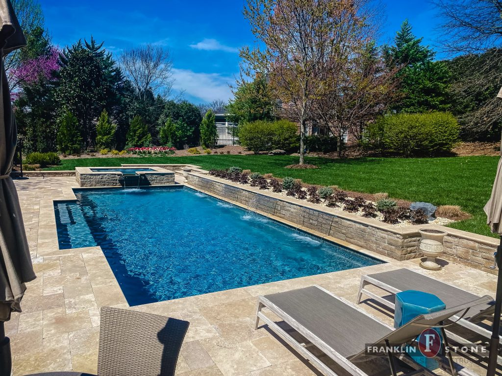 Franklin Stone pool and stone spa with running water features and lounge chairs