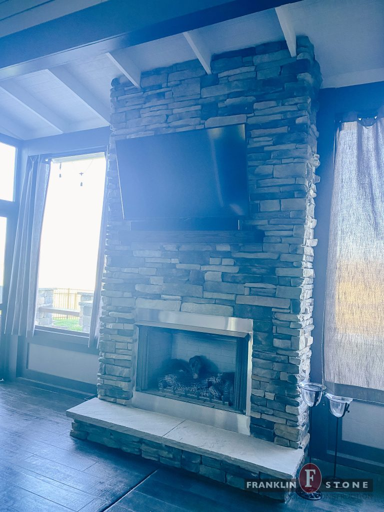 Franklin Stone indoor fireplace with mounted TV
