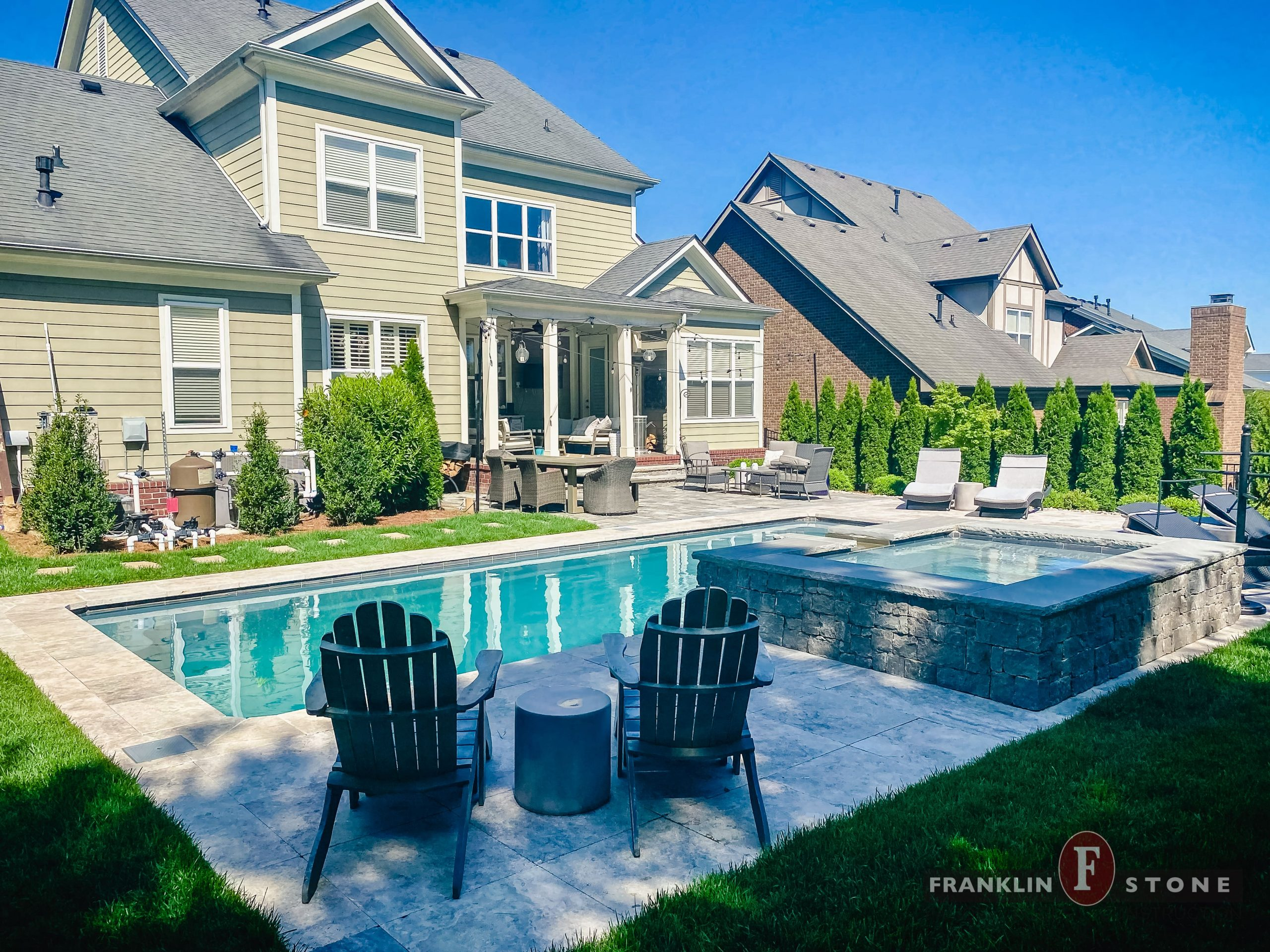 Franklin Stone pool and stone spa with outdoor patio furniture