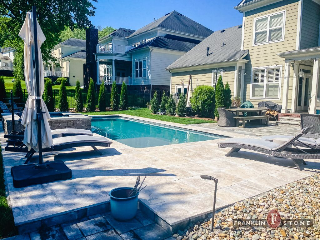 Franklin Stone pool and stone spa with outdoor patio seating