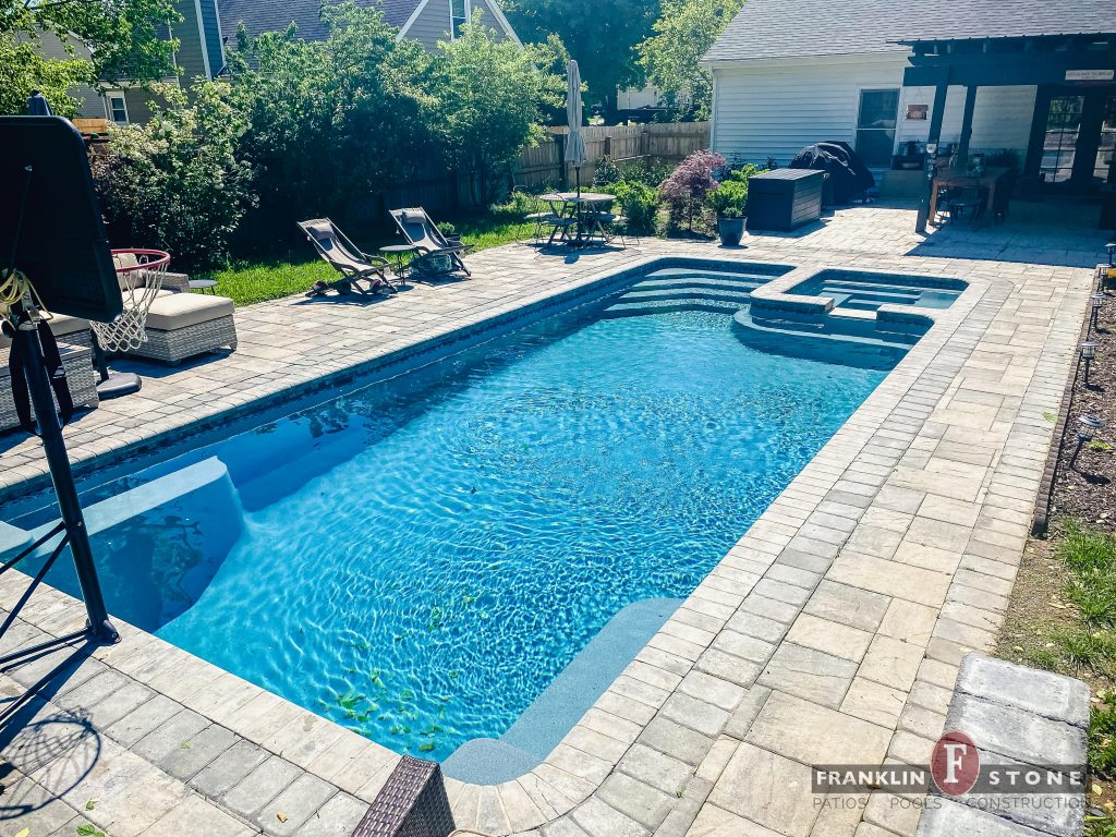 Franklin Stone pool and spa with basketball hoop and outdoor patio furniture