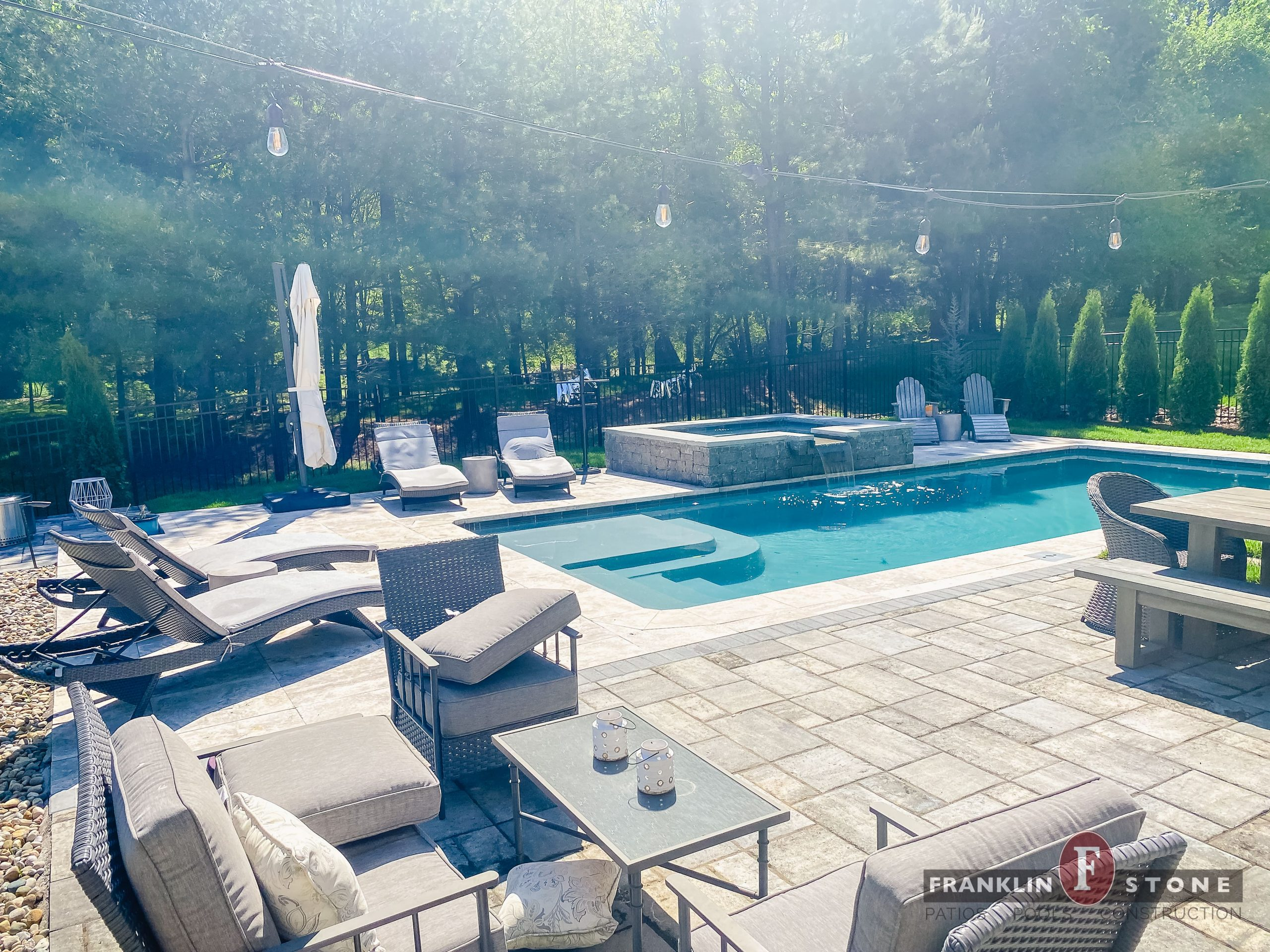 Franklin Stone pool and spa with running water features and surrounded by outdoor patio seating areas